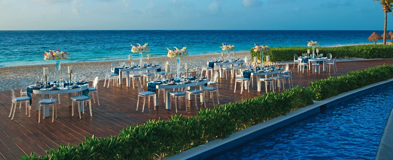 Beach-front setup for a dinner gala on the deck during the day.