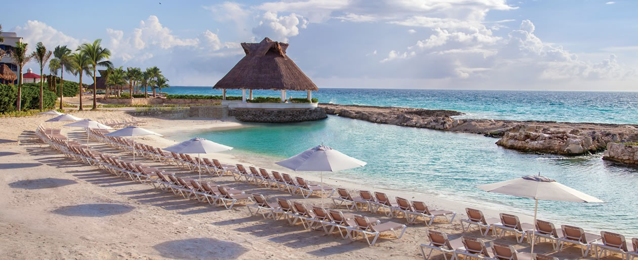 The Hard Rock Hotel Riviera Maya Where Paradise Comes To Play on the beach and resort lagoon with umbrellas.