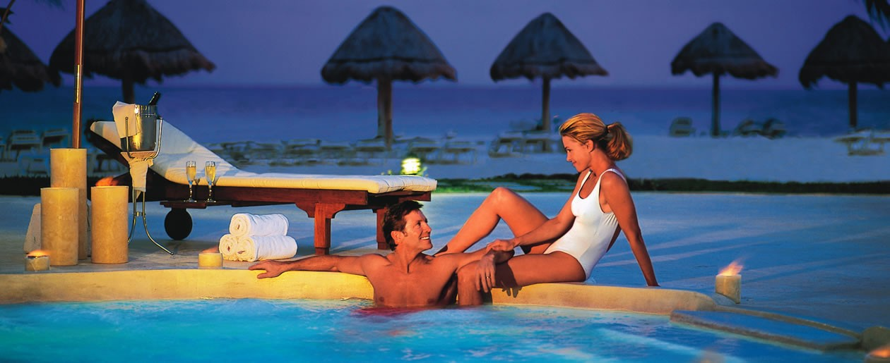 A couple lounging in the Jacuzzi at Secrets Capri at dusk.