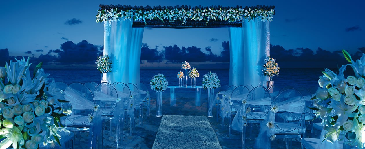 Floral arrangements add to the stunning ambiance of this beach wedding ceremony.